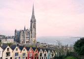 Cork, Ireland - March 24, 2012: St. Colman's Cathedral situated in Cobh, Cork photographed at sunset with a row of multi-colored terraced houses in the foreground.