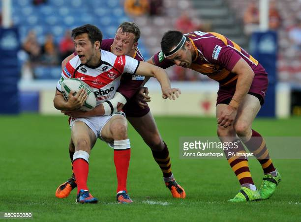 St Helens' Gareth O'Brien is tackled by Huddersfield Giants' Danny Brough and Shaun Lunt during the Super League match at the John Smith's Stadium...