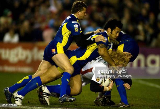 St Helen's James Graham is brought ground by Warrington's Lee Briers and Paul Rauhihi during the engage Super League match at Knowsley Road St Helens