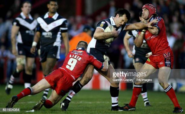 St Helens' Paul Sculthorpe hands off Salford's Simon Baldwin as he is tackled by Malcolm Alker during the engage Super League match at The Willows...