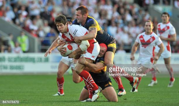 St Helens Richard McCarthy Scarsbrook is tackled by Leeds Rhinos Chris Clarkson and Paul McShane during the Stobart Super League match at Langtree...
