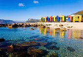 Crystal clear water of St James Beach and tidal pool with its colourful huts, Cape Town, South Africa