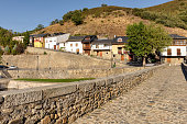 View of St James way path at historic Roman bridge in Molinaseca, Castile and Leon, Spain.