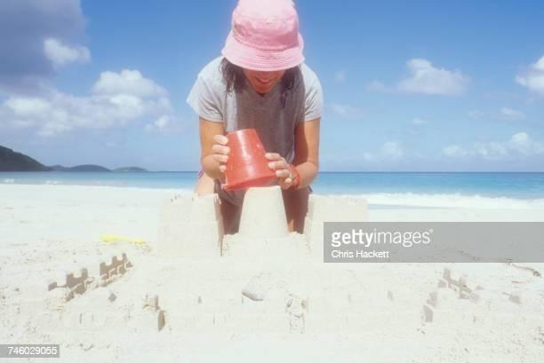 USA, USVI, St. John, Mature woman in pink sun hat making sandcastle on beach