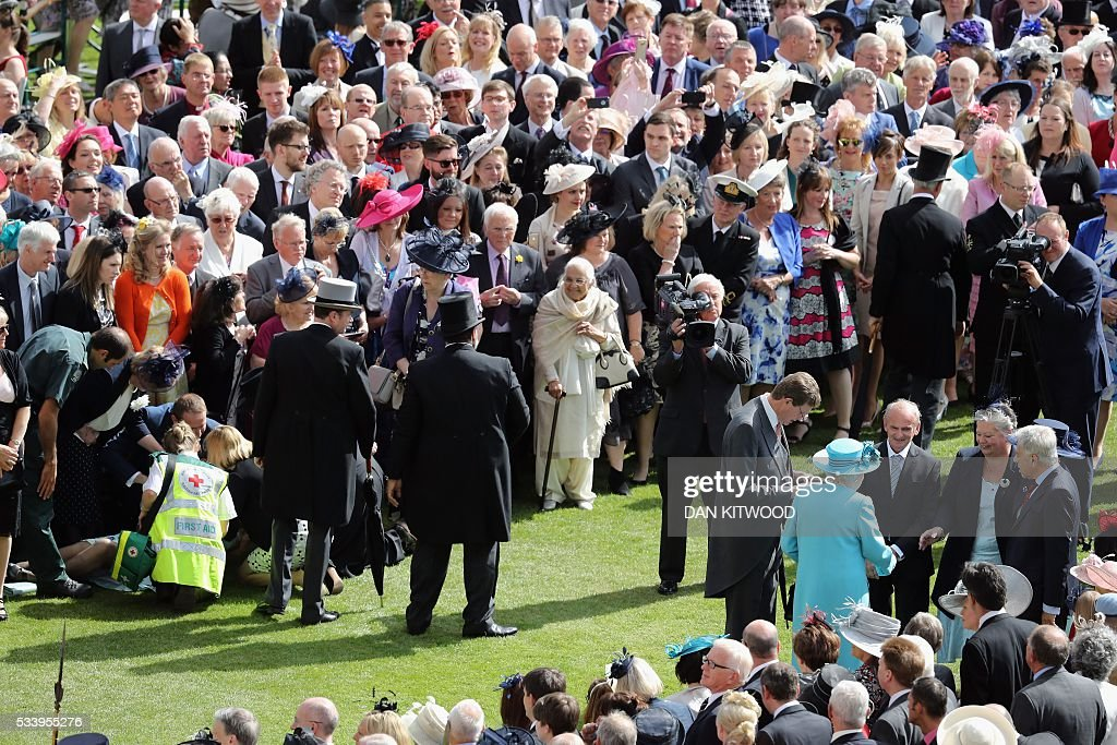 St John's ambulance crew attend to a lady who had fallen as Britain's Queen Elizabeth II (in blue) greets guests attending a garden party at Buckingham Palace in London on May 24, 2016. / AFP / POOL / Dan Kitwood