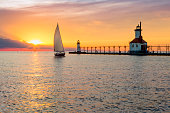 A sailboat rounds the breakwater near sunset on the longest day of the year by the Lighthouses at St. Joseph, Michigan with people fishing from and walking on the pier.