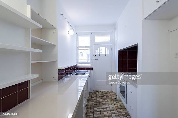 A kitchen in an empty rental apartment freshly painted in white.