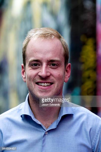 A young, confident and progressive businessman smiling in a collared shirt.