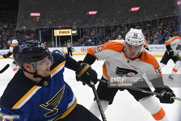 St Louis Blues defenseman Colton Parayko and Philadelphia Flyers center Jori Lehtera battle for a loose puck during a National Hockey League game...