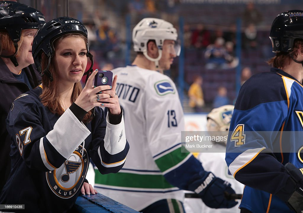 St. Louis Blues fan takes photos on her iPhone before an NHL game against the Vancouver Canucks on April 16, 2013 at Scottrade Center in St. Louis, Missouri.