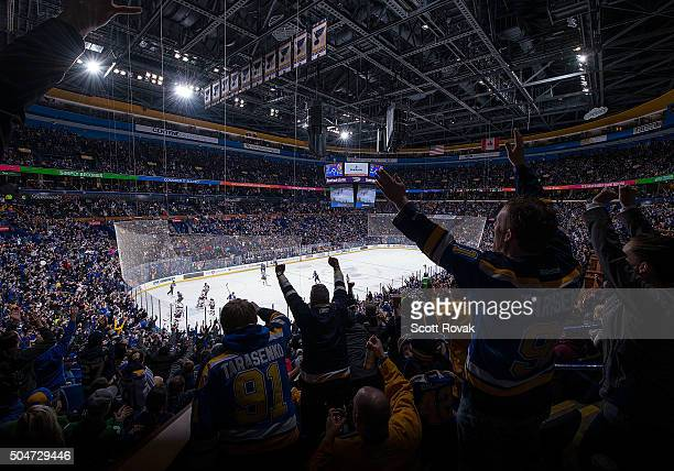 St Louis Blues fans celebrate after their team scored a goal against the New Jersey Devils at the Scottrade Center on January 12 2016 in St Louis...