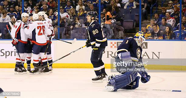 St Louis Blues goaltender Brian Elliott right picks up his stick as Washington Capitals players celebrate defenseman John Carlson's goal in the...