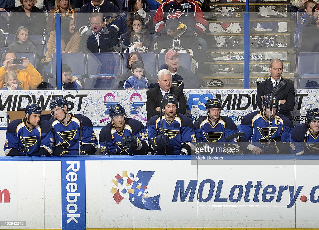 St. Louis Blues head coach Ken Hitchcock stands in front of a banner for Pink in the Rink in association with breast cancer prevention in an NHL game against the Edmonton Oilers on February 28, 2013 at Scottrade Center in St. Louis, Missouri.