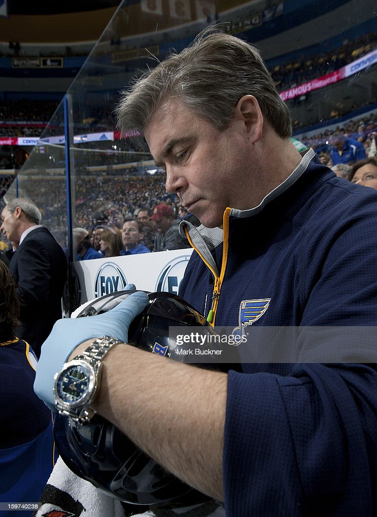 St. Louis Blues medical trainer Ray Burile wipes off the face shield of T.J. Oshie #74 in an NHL game against the Detroit Red Wings on January 19, 2013 at Scottrade Center in St. Louis, Missouri.