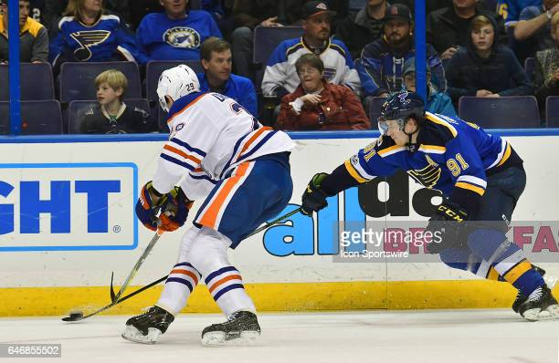 St Louis Blues rightwing Vladimir Tarasenko tries to poke the puck away from Edmonton Oilers' center Leon Draisaitl during a NHL game game between...