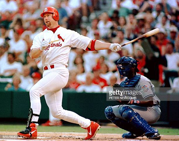 St Louis Cardinal first baseman Mark McGwire hits a single as Los Angeles Dodger catcher Charlie Johnson looks on in the third inning 19 July in St...