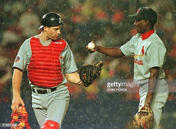 St Louis Cardinal pitcher Manny Aybar hands the ball to catcher Mike DiFelice during rain in third inning of game 04 August against the New York Mets...