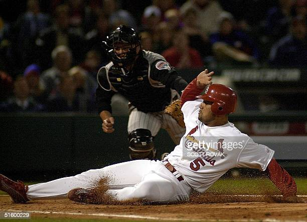 St Louis Cardinals' Albert Pujols slides home safely before a late tag by Arizona Diamondbacks' Damian Miller in the sixth inning 16 April 2001 in St...