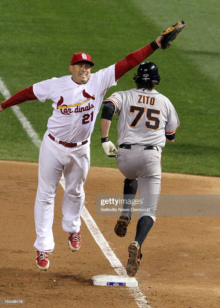 St. Louis Cardinals first baseman Allen Craig (21) is pulled off the bag on a throw from third baseman David Freese as Barry Zito (75) of the San Francisco Giants reaches safely on a bunt in the fourth inning in Game 5 of the National League Championship Series at Busch Stadium in St. Louis, Missouri, on Friday, October 19, 2012.
