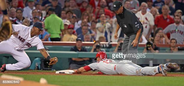St Louis Cardinals' Matt Carpenter is safe at third base with a headfirst slide as he beats the tag of Red Sox player Rafael Devers in the top of the...