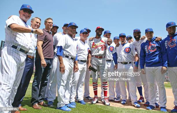 St Louis Cardinals outfielder Dexter Fowler middle poses for photographs with former teammates after accepting his World Series Championship ring at...