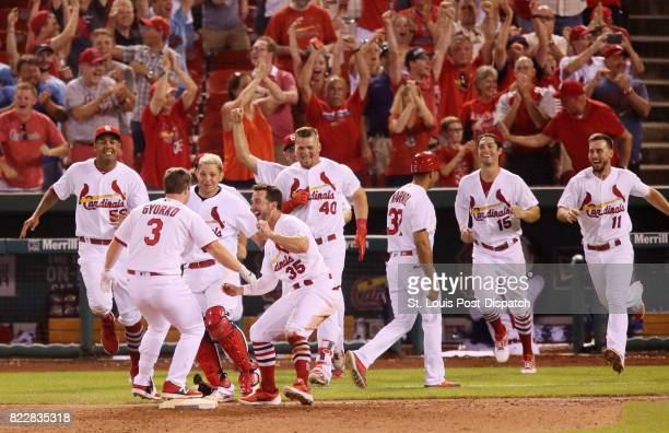 St Louis Cardinals pinch hitter Jedd Gyorko is swarmed by teammates after he drove in the gamewinning run with a sacrifice fly in the ninth inning...
