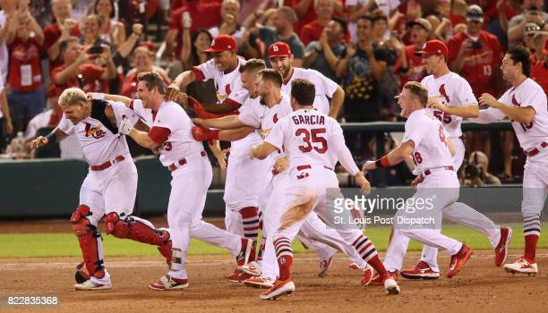 St Louis Cardinals pinch hitter Jedd Gyorko second from left is swarmed by teammates after he drove in the gamewinning run with a sacrifice fly in...