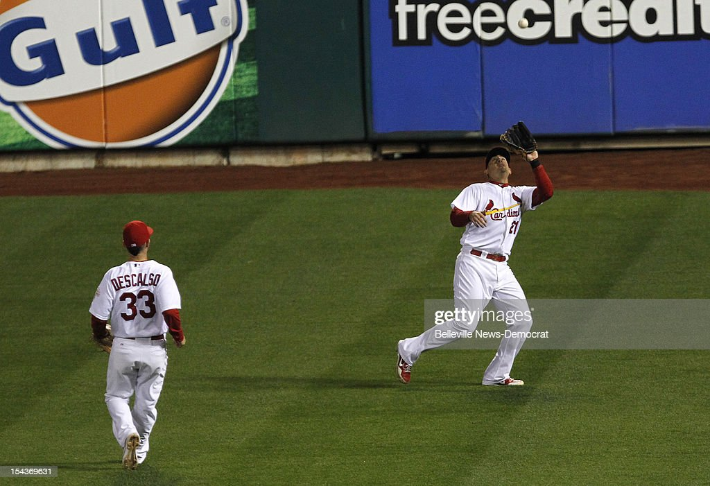 St. Louis Cardinals right fielder Allen Craig, right, reaches to catch a fly ball in the seventh inning against the San Francisco Giants in Game 4 of the National League Championship Series at Busch Stadium in St. Louis, Missouri, on Thursday, October 18, 2012. The Cardinals won, 8-3, to take a 3-1 series lead.