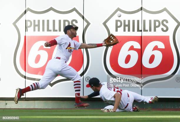 St Louis Cardinals right fielder Stephen Piscotty right drops out of the way as center fielder Tommy Pham catches a fly ball by Pittsburgh Pirates'...