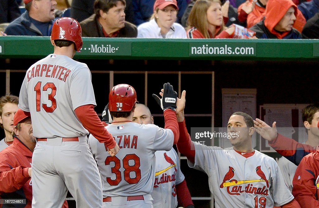 St. Louis Cardinals shortstop Pete Kozma (38) and Cardinals second baseman Matt Carpenter (13) are welcomed in the dugout after scoring a 2-RBI double by teammate Allen Craig in the third inning against the Washington Nationals at Nationals Park in Washington, D.C., Monday, April 22, 2013.