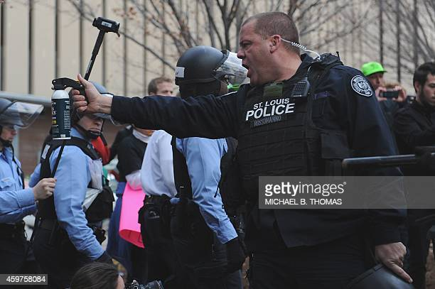 A St Louis City police officer threatens demonstrators with a can of pepper spray in downtown St Louis Missouri on November 30 2014 Demonstrators...