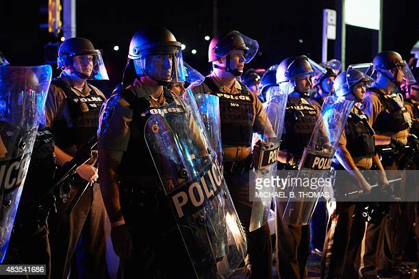 St Louis County Police and Missouri State Highway Patrol troopers stand guard as protesters march on West Florissant Avenue in Ferguson Missouri on...