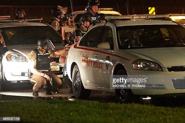 A St Louis County police officers takes cover behind a car after shots were fired during a protest march on August 9 2015 on West Florissant Avenue...