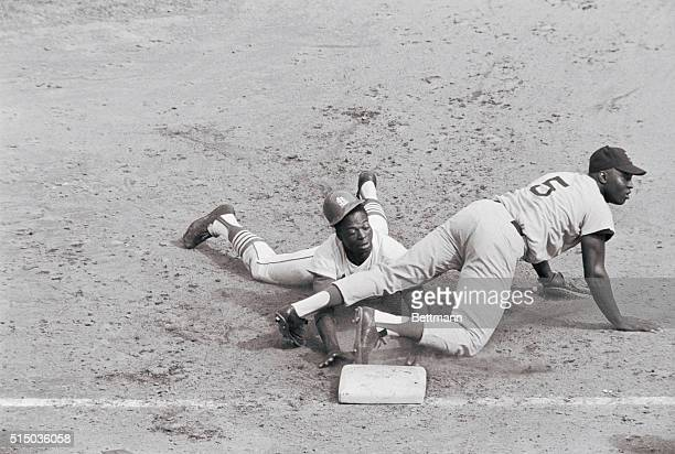 Lou Brock's helmet falls off as Cards' speedster hustles back to 1st on pick off try in 6th inning of 3rd game of World Series Boston 1st baseman...