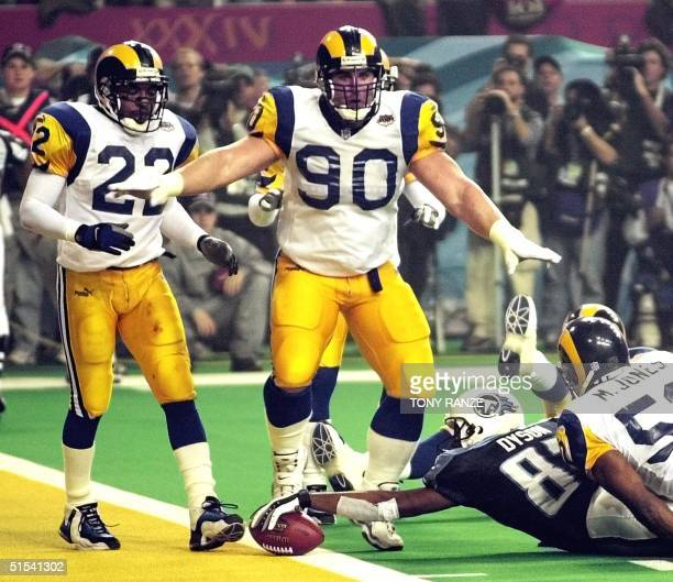 St Louis Rams defensive player Jeff Zgonina signals no touchdown as Tennessee Titans wide receiver Kevin Dyson stretches the ball over the goal line...