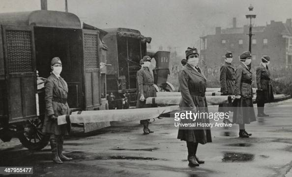 St Louis Red Cross Motor Corps on duty during the American Influenza epidemic 1918 maskwearing women holding stretchers at backs of ambulances