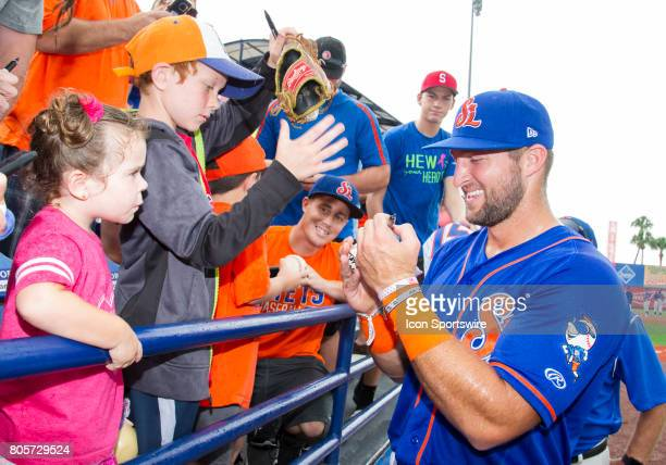 St Lucie Mets Outfielder Tim Tebow smiles as he signs autographs for fans in the stands before the start of the first game of a double header MiLB...