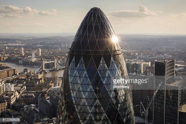 30 St Mary Axe also known as the Gherkin stands surrounded by commercial office buildings as the Tower of London and Tower Bridge sit beyond in this...