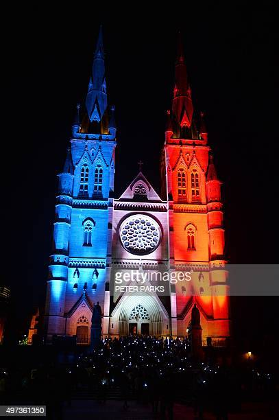 St Mary's Cathedral in Sydney is lit up in the French tricolor to remember the victims of the Paris terrorist attacks as people gather outside after...