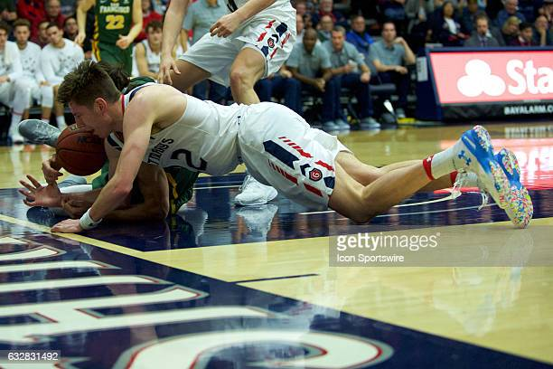 St Mary's Gaels forward Dane Pineau and San Francisco Dons forward Matt McCarthy dive for the ball during the first half of the Gaels' 6646 victory...