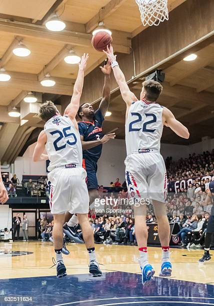 St Mary's Gaels forward Dane Pineau gets a hand on a shot by Pepperdine Waves guard Jeremy Major during the regular season game between Pepperdine...