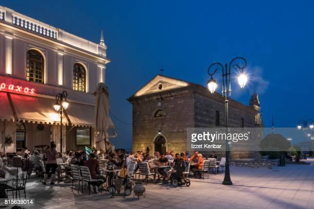 St Nicholas church and part of illuminated building  and people in café at Solomos square at the blue hour Zakynthos, Ionian Islands Greece