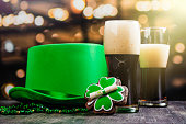 Two glasses of ale and St Patricks day accessories. Bar background. Copy space