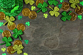 St Patricks Day corner border with shamrocks, gold coins and leprechaun hat over a dark slate background