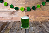St. Patrick's mug of green beer on wooden background. Tabletop, front view.