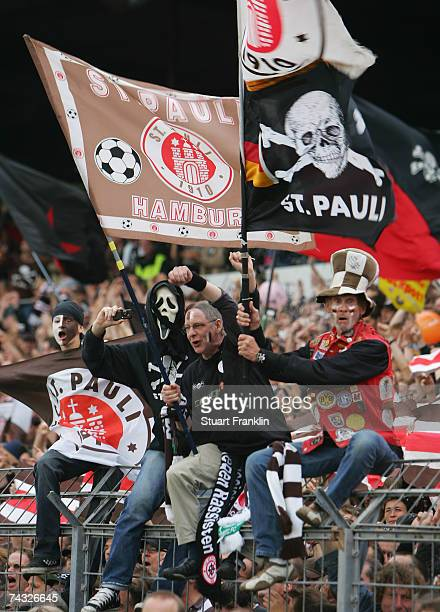 St Pauli fans wave flags in support of their team during the Third League Northern Division match between FC StPauli and Dynamo Dresden at the...