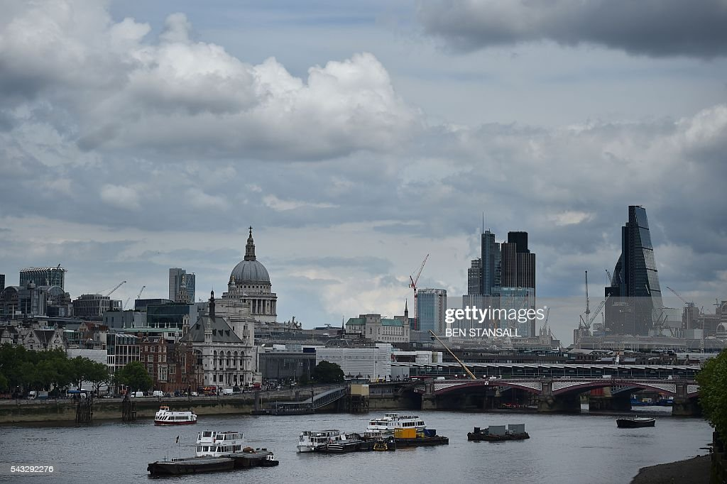 St Paul's Cathedral and buildings in City of London are seen under banks of cloud in central London on June 27, 2016. Britain began preparations to leave the European Union on Monday but said it would not be rushed into a quick exit, as markets plunged in the wake of a seismic referendum despite attempts to calm jitters. / AFP / BEN