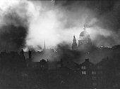 St Paul's Cathedral seen through the flames and smoke of blazing buildings in the City of London during the Blitz