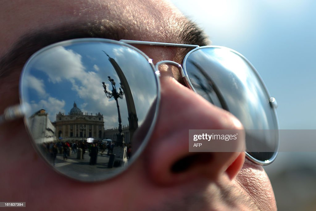 St Peter's basilica is reflected on the sunglasses of a faithful during the Angelus prayer led by Pope Benedict XVI from the window of his appartments on February 17, 2013 at the Vatican. The Vatican the day before said it could speed up the election of a new pope as lobbying for Benedict XVI's job intensified amid speculation over who had the best chance to succeed him. AFP PHOTO / GABRIEL BOUYS