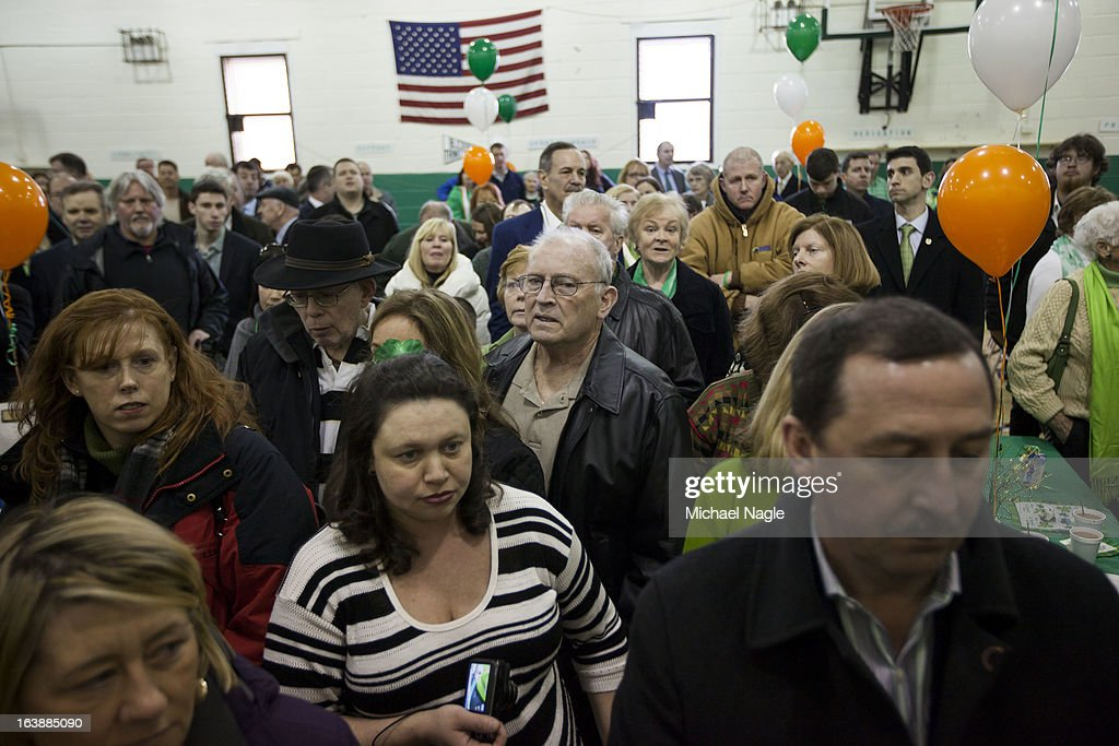St Thomas More parishioners listen the the Irish national anthem after Saint Patrick's Day Mass on March 17, 2013 in the Breezy Point neighborhood in the Queens borough of New York City. Breezy Point, home to many residents with Irish ancestry, was devastated by Superstorm Sandy in October 2012.